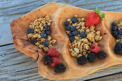 Hand carved wood bowl with fresh berries and granola Royalty Free Stock Photo
