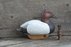 Hand carved wooden duck decoy. Wooden duck decoy and duck call with a weathered wood background Stock Image
