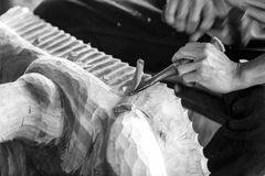 Hand of carver carving wood in black and white color tone Stock Image