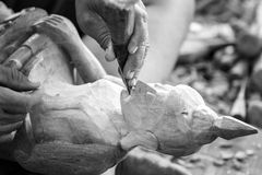 Hand of carver carving wood in black and white color tone Stock Photos