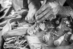 Hand of carver carving wood in black and white color tone Royalty Free Stock Photo