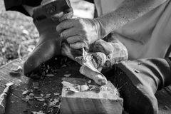 Hand of carver carving wood in black and white color tone Royalty Free Stock Photography