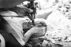 Hand of carver carving wood in black and white color tone Royalty Free Stock Images