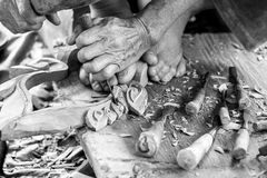 Hand of carver carving wood in black and white color tone. Photo Hand of carver carving wood in black and white color tone Royalty Free Stock Photos