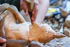Hand of carver carving wood Stock Images