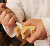 Hand carving an animal from piece of wood Royalty Free Stock Photo