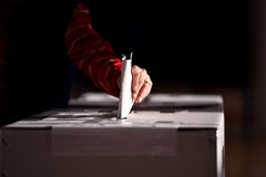 Hand casting a vote into the ballot box. Hand of a person casting a vote into the ballot box during elections Royalty Free Stock Photo
