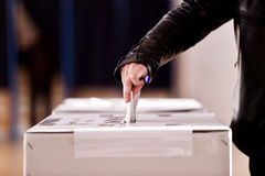 Hand casting a vote into the ballot box. Hand of a person casting a vote into the ballot box during elections stock photos