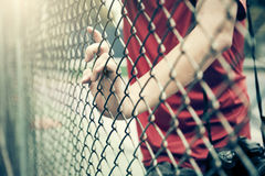 Hand catching mesh cage.. The prisoner want freedom. Royalty Free Stock Photo