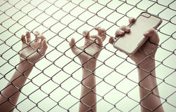 Hand catching mesh cage.. The prisoner want freedom. Dramatic Blurry Hands catching mesh cage. The prisoner want freedom.Man lack of Independence Stock Photography