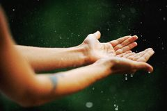 Hand catching rain drops. On blurred background Royalty Free Stock Image