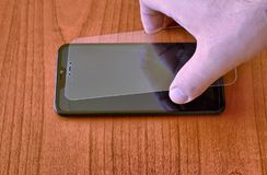 Preparation of the material to install a protective glass cover on the smartphone screen royalty free stock image