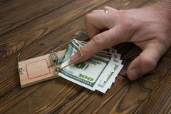 Hand caught in a mousetrap with one hundred dollars banknote. The concept of fraud, bribe, capture of the initiator. business risk. caught stealing royalty free stock photography
