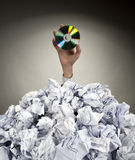 Hand with CD reaches out from heap of papers Stock Photography