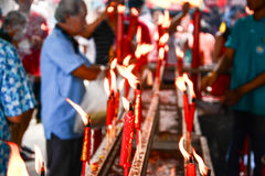 Hand cense joss stick to  burning candle Royalty Free Stock Image