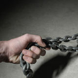 Hand on chain. Strong hand of industrial worker pulling chain sideways. Copy space available. Close up photo, square version Royalty Free Stock Photo