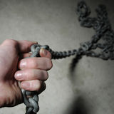 Hand on chain. Strong hand of industrial worker holding chain. Copy space available. Close up photo, square version Royalty Free Stock Photos