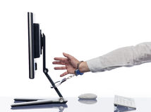 Hand chained to computer with handcuffs Royalty Free Stock Photos