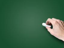 Hand with chalk on blank blackboard Stock Photography