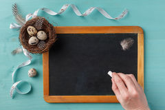 Hand with chalk, chalkboard and easter decor Royalty Free Stock Photo