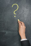 Hand with chalk drawing a question sign Stock Image