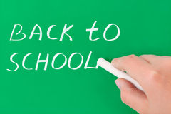 Hand with chalk writing Back to school. On blackboard Royalty Free Stock Photography