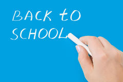 Hand with chalk writing Back to school. On blackboard Royalty Free Stock Image