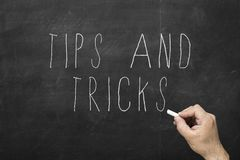 Hand with chalk writing Tips and Tricks concept on black chalkboard. royalty free stock images