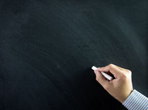 Hand on chalkboard. Close up of hand holding chalk on blank chalkboard Royalty Free Stock Image