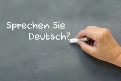 Hand on a chalkboard with the German words Sprechen Sie deutsch Royalty Free Stock Photography