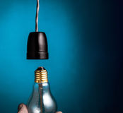 Hand changing a antique edison style filament light bulbs on dar Royalty Free Stock Images