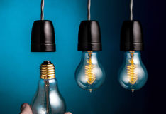Hand changing a antique edison style filament light bulbs on dar Stock Image