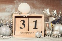 Hand changing wooden calendar with different New Year decorations stock image