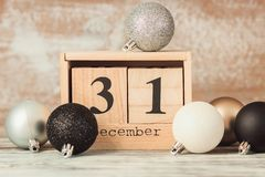 Hand changing wooden calendar with different New Year decorations royalty free stock photography