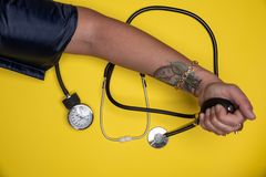 Hand checking blood pressure and stethoscope set aside royalty free stock images