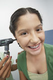Hand Checking Happy Girl's Ear With Otoscope. Closeup of hand checking happy teenage girl's ear with otoscope stock image