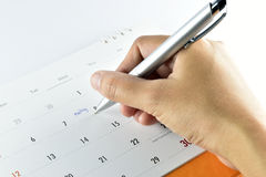 Hand checking meeting plan in calendar. Stock Photo