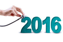 Hand checking numbers 2016 with stethoscope Royalty Free Stock Photo