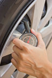 Hand checking tire pressure. Royalty Free Stock Image