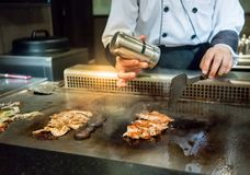Hand of Chef adding salt into the steak on hot pan in front of c stock images