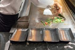 Hand of Chef cooking salad on hot pan in front of customers. Japanese Tepanyaki Steak Stock Photography