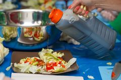 Chef pouring sauce on salad, cooking process, restaurant concept Royalty Free Stock Photos