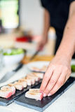 Hand of Chef preparing sushi in the kitchen Stock Photos
