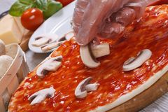 Hand chef puts on a pizza base champignons Royalty Free Stock Photos