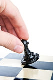 Hand and a chess pawn on the board Stock Photography