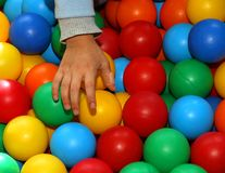Hand of a child with a band-aid that takes the colored balls Royalty Free Stock Image