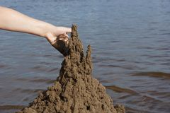 The hand of the child builds a sand castle on the beach on the b. Ackground of water summer day royalty free stock photography