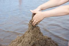 The hand of the child builds a sand castle on the beach on the b. Ackground of water summer day stock image