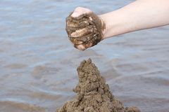 The hand of the child builds a sand castle on the beach on the b. Ackground of water summer day stock images