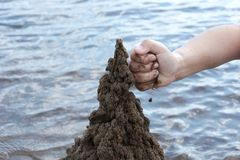The hand of the child builds a sand castle on the beach on the b. Ackground of water summer day stock photo